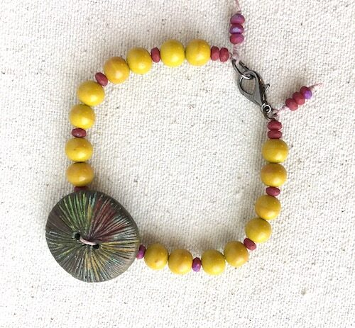 Mustard yellow and mauve bead bracelet with colorful button focal