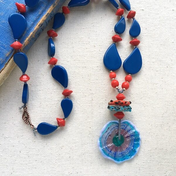 Blue paisley shaped beads with red accent beads and wavy donut glass pendant.