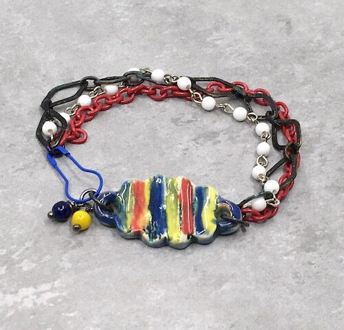 Yellow, red and blue ceramic bracelet bar with white rosary chain, rustic black metal diamond chain and red enamel link chain with blue carabiner pin clasp.