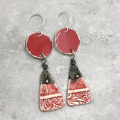 Red and silver earrings with rustic red tin round discs with patterned red and white ceramic headpin drops topped with darkened patterned tinwork.