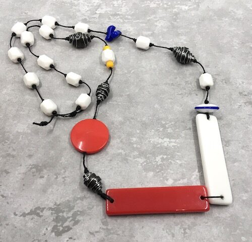 Necklace with red and white long rectangular connectors knotted on black waxed linen with white hex beads, rolled black and grey metal beads, small blue and yellow beads, a red disk and a blue and white disk.