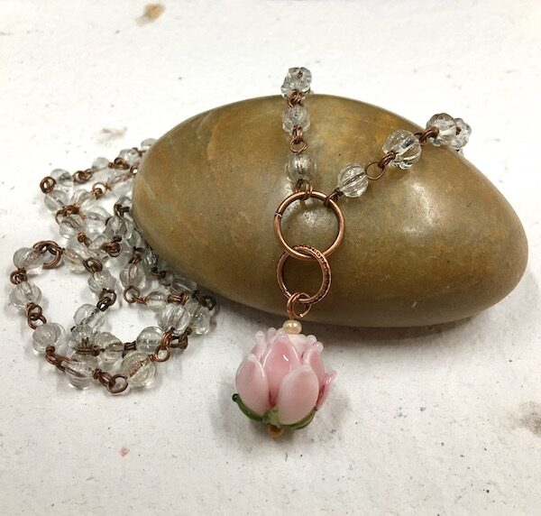 Necklace of a delicate pink lampwork glass flower bead with green leaves on copper jump rings with clear glass beaded rosary chain.